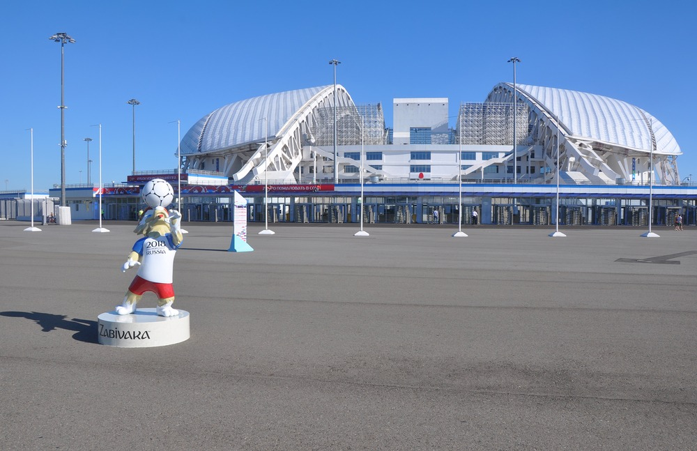 Det olympiske stadion i Sotji set udefra. I forgrunden ses en statue af VM-maskotten Zabivaka.