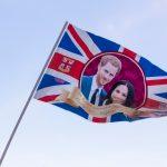 Britisk flag med prins Harry og Meghan Markles ansigter på foran blå himmel