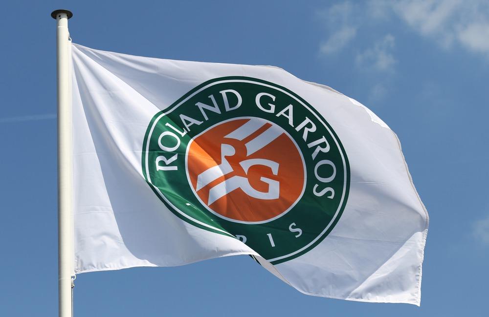 Hvidt flag med French Opens logo med en blå himmel i baggrunden
