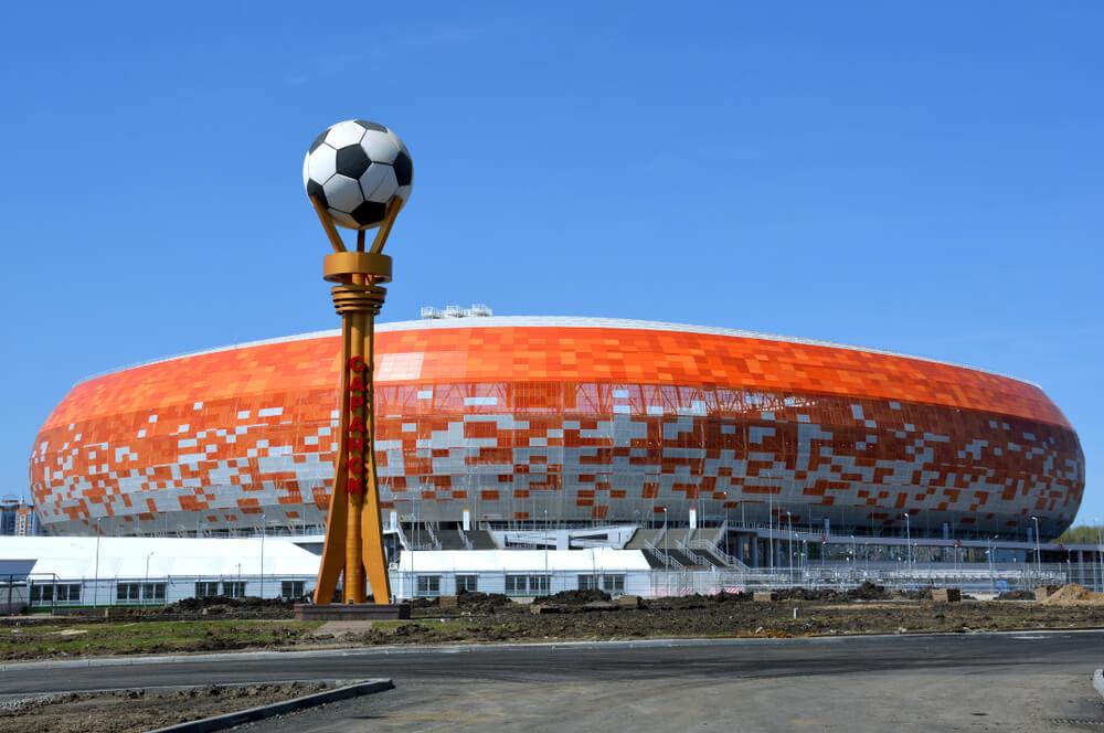 VM-stadionet Mordovia Arena. I forgrunden ses en statue med en fodbold og i baggrunden er stadionet